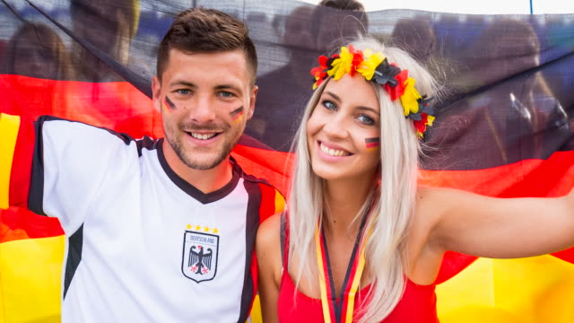 CU german sport fans celebrating at soccer stadium, portrait