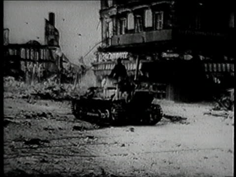 vídeos de stock e filmes b-roll de german tank driving past destroyed buildings / burning buildings - infantaria