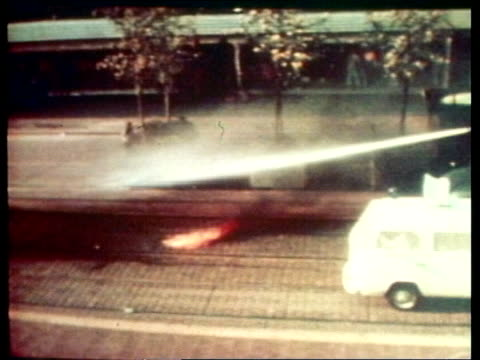 german terrorism itn lib ts fire burning in street as water cannon onto it pan lr water cannon spraying demos - terrorismus stock-videos und b-roll-filmmaterial