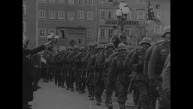 vidéos et rushes de german troops marching into austrian city, cheering crowds on sidelines, nazi flags flying / soldiers marching in street, arm making nazi salute from... - nazism