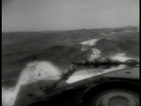 german u-boat at sea heavy waves. vs german sailors w/ raincoats. vs violent seas waves. silhouette of ship on fire smoke. german sailors firing... - 1941 stock videos & royalty-free footage