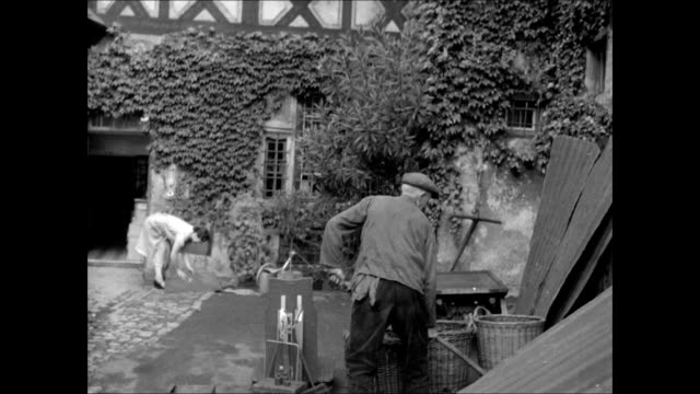 German woman turning rugs outside home / w male shoveling near baskets Senior female shopping at butcher shop counter holding change purse WS Alpine...
