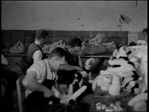german workers assemble stuffed animals / a woman sews a stuffed animal / detail of a stuffed dog / a man builds a lamb body / he inserts a fluffy... - ぬいぐるみ点の映像素材/bロール
