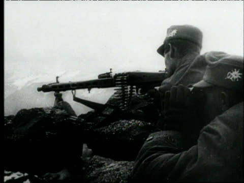 germans climbing up mountains / russian soldiers digging into snowy mountain to fight nazis / soldiers firing machine guns / soldiers climbing over... - 1942年点の映像素材/bロール