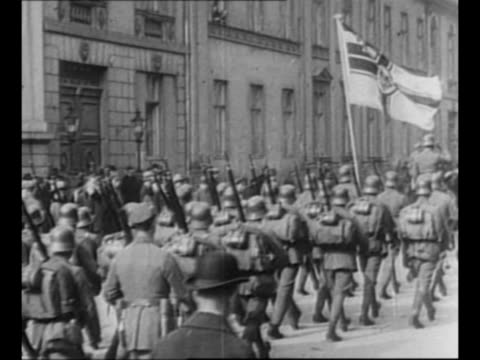 germans march in streets / rear shot german troops march, bearing flag featuring the war ensign of germany / mounted soldiers with war ensign flag,... - german military stock videos & royalty-free footage