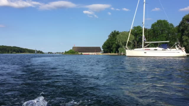 vidéos et rushes de germany, bavaria, lake chiemsee, yacht or motor boat cruising near island herrenchiemsee or herreninsel - aller tranquillement