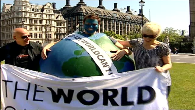 London protests Annie Lennox and Midge Ure photocall with man in globe costume and 'World Can't Wait' banner