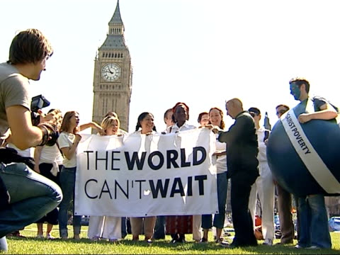 london protests demonstration scenes ure standing in front of protestors holding banner 'the world can't wait' and another dressed as the world with... - g8 stock-videos und b-roll-filmmaterial