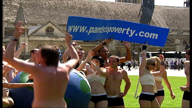 london protests 'pants to poverty' protestors wave banners in parliament square - g8 stock-videos und b-roll-filmmaterial