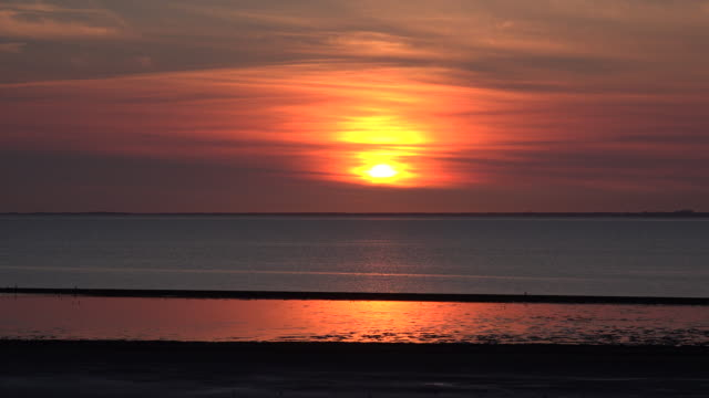 Germany reflections of setting sun on water of Wadden Sea