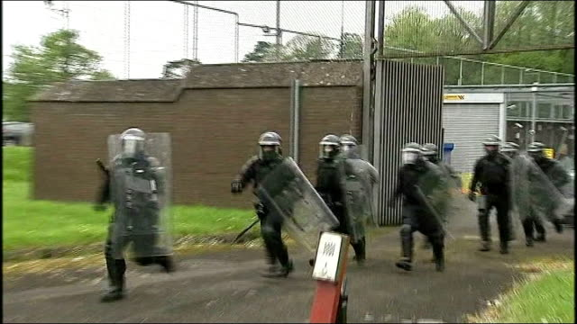 gerry adams receives 'credible' death threat following his release from police questioning group of riot police running from police station car... - gerry adams stock videos and b-roll footage