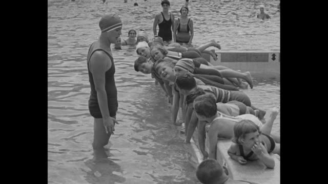 gertrude ederle standing in front of row of children lying on edge of pool she tells them to make swimming motion with their arms and children move... - gertrude ederle stock videos & royalty-free footage
