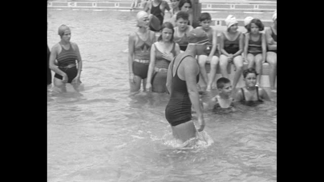 gertrude ederle standing in pool surrounded by children sitting on edge of pool and row of children on either side of her in pool small boy asks her... - gertrude ederle stock videos & royalty-free footage