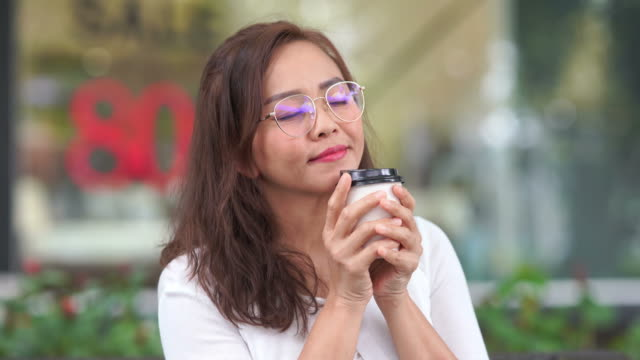 Gesturing by Asian luxury mature woman at coffee shop, day dreaming with coffee aroma