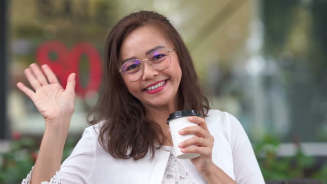 Gesturing by Asian luxury mature woman at coffee shop, hello and goodbye sign