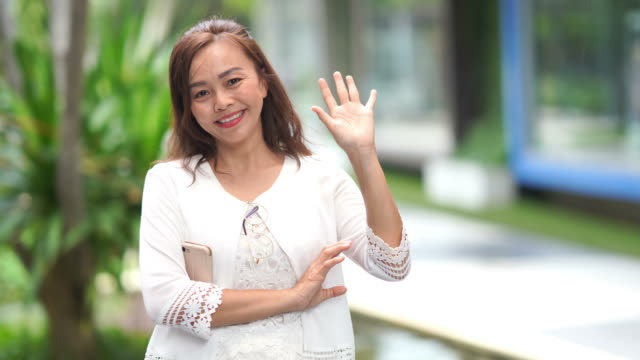 Gesturing by Asian luxury mature woman, hello and goodbye sign  , slow motion