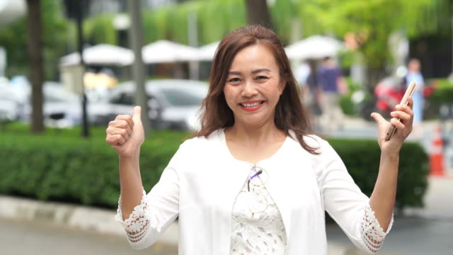 Gesturing by Asian luxury mature woman, pride and success sign