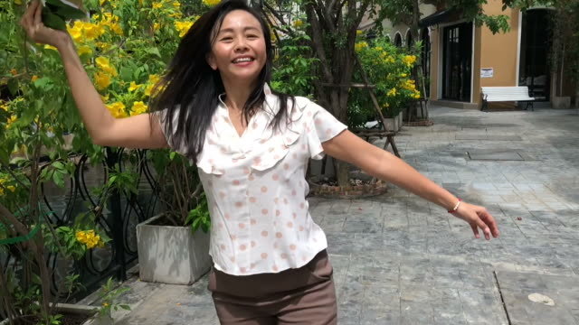 gesturing by mature Asian woman , slow motion