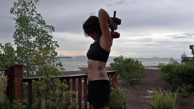 vídeos y material grabado en eventos de stock de ponte en forma a casa entrenamiento mujer extensión de tríceps con peso - miembro humano