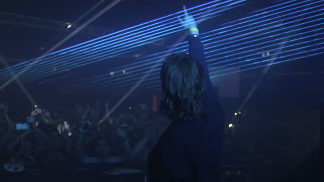 vidéos et rushes de dj gets crowd going at remembrance festival, lasers shoot across room - dj