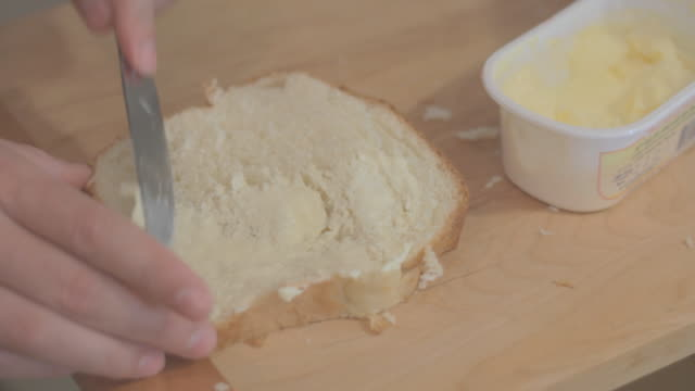 getting butter spread from container and spreading it onto bread. - white bread stock videos and b-roll footage