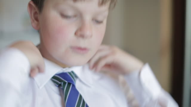 getting dressed for school - boy turning down his shirt collar - schoolboy stock videos and b-roll footage