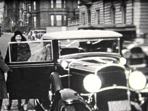 1930 getting into fancy car on new york street - anno 1930 video stock e b–roll