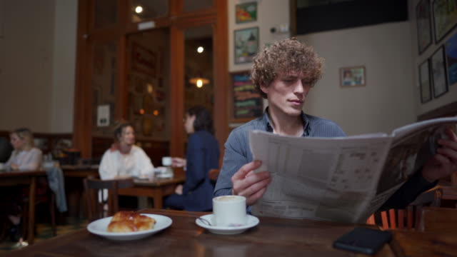 vídeos de stock, filmes e b-roll de recebendo minhas notícias diárias do meu café favorito - jornal