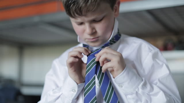getting ready for school - boy tying his school tie - fastknäppt skjorta bildbanksvideor och videomaterial från bakom kulisserna