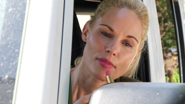 vorbereitung auf das treffen, frau ansiebt lippenstift im autospiegel - lippen stock-videos und b-roll-filmmaterial