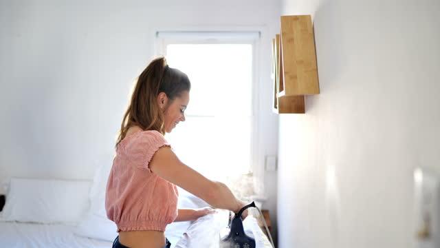 仕事の概念に準備する:焦点を当てた若い女性 - アイロン台点の映像素材/bロール