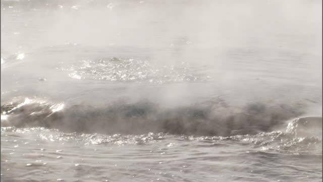vídeos de stock, filmes e b-roll de a geyser builds pressure then erupts in strokkur iceland. available in hd. - gêiser strokkur
