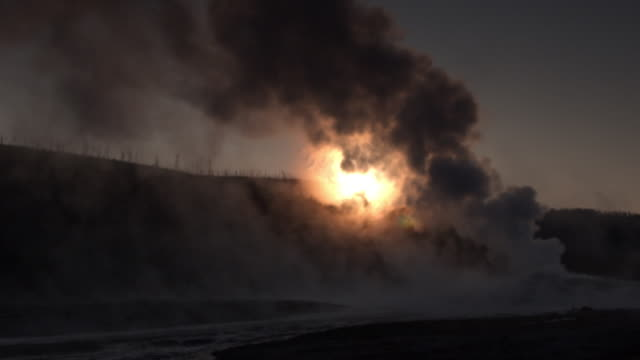 geyser erupts in front of setting sun. - geyser video stock e b–roll