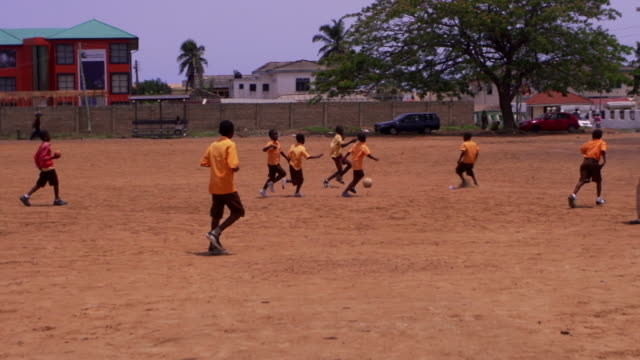 Ghanian boys play football in a dirt lot