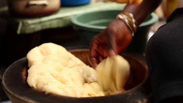 A Ghanian woman kneads cassava fufu dough