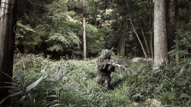 ghillie suit sniper in the jungle standing up with rifle - camouflage stock videos & royalty-free footage