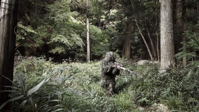 ライフルで立ち上がるジャングルのギリースーツ狙撃兵 - 戦争点の映像素材/bロール