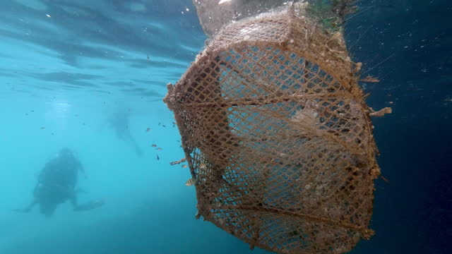 ghost net pollution in sea near scuba divers thailand underwater pov - andaman sea stock videos & royalty-free footage