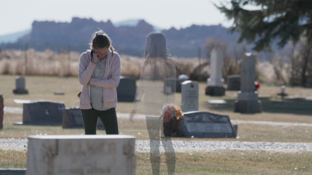 ghost of girl comforting sister crying near gravestone in cemetery / bicknell, utah, united states - two people stock videos & royalty-free footage
