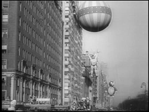 b/w 1945 giant balloons near buildings in macy's thanksgiving day parade on central park west / nyc - 1945 stock videos & royalty-free footage