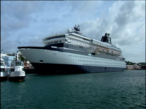 giant cruise liner docked in harbour flanked by small tug boats; bermuda - 大西洋諸島点の映像素材/bロール