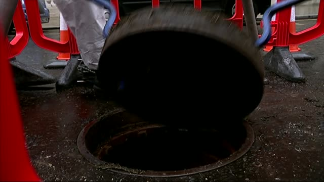 vídeos y material grabado en eventos de stock de giant fatberg discovered in sewer under clerkenwell; t03111415 london thames water engineers removing manhole cover to sewer int build up of fat -... - tapadera de cloaca
