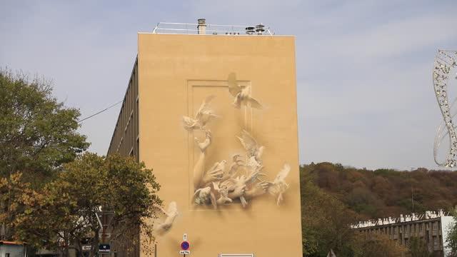 vidéos et rushes de giant fresco on the facade of a social housing building in the 'bernard de jussieu' district represents doves flying away on november 7 in... - hlm