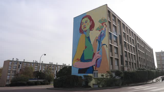 vidéos et rushes de giant fresco on the facade of a social housing building in the 'bernard de jussieu' district represents a woman with a bouquet of flowers on november... - hlm