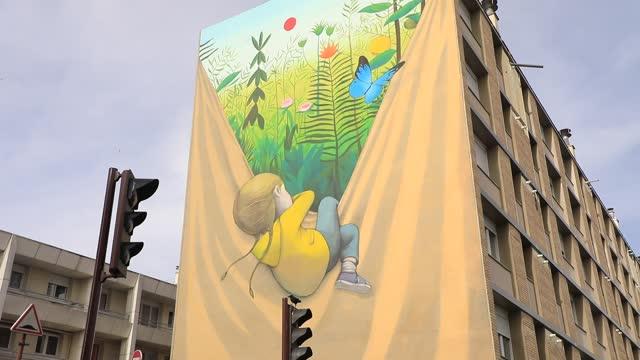 vidéos et rushes de giant fresco on the facade of a social housing building in the 'bernard de jussieu' district represents a child who discovers a world full of colours... - hlm