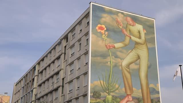 vidéos et rushes de giant fresco on the facade of a social housing building in the 'bernard de jussieu' district represents a figure taking care of flowers on november 7... - hlm