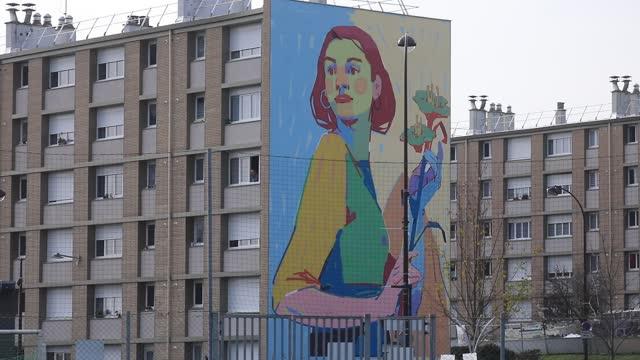 vidéos et rushes de giant fresco on the facade of a social housing building in the 'bernard de jussieu' district represents a woman with a bouquet of flowers on november... - problème de logement