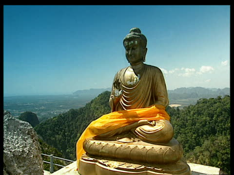 giant golden buddha statue wrapped in huge orange sarong high on a hillside surrounded by lush green forest with blue skies in background; thailand - buddha stock-videos und b-roll-filmmaterial