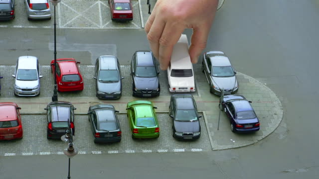 stockvideo's en b-roll-footage met giant hand is swapping cars on parking - klein