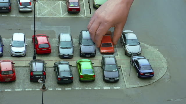 stockvideo's en b-roll-footage met giant hand is swapping cars on parking - steel